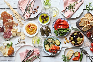 Mediterranean appetizers table concept. Dinner table with tapas selection: cured meat and salami, gazpacho soup, jamon, olives, cheese, hummus and vegetables. Overhead view.