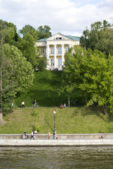 People walk along the embankment along the Moscow river.