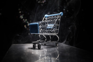 shopping trolley on dark toned foggy background with some copy space