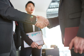 Business people concluding a deal. Two businessmen in suit shaking hands