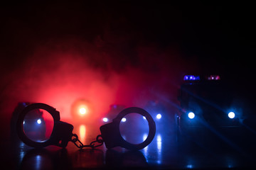 Closed handcuffs on the street pavement at night with police car lights Fotomurales