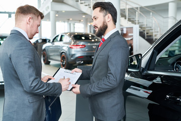 Young man in suit signing a contract for purchase the new car