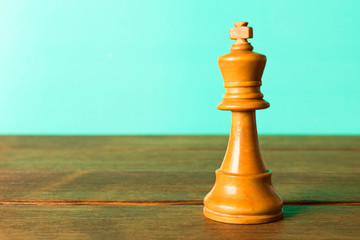 Chess king on a wooden table. On a turquoise background. Close up
