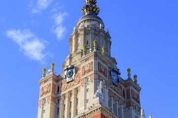 Fragment of Lomonosov Moscow State University (MSU) tower with national emblem of USSR on a blue sky background