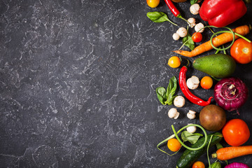 Raw organic vegetables with fresh ingredients for healthily cooking on vintage background, top view. Vegan or diet food concept