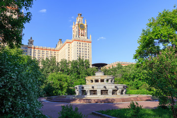 East fountain in the park against buildings of Lomonosov Moscow State University (MSU) in sunny summer evening
