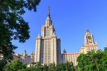 Lomonosov Moscow State University (MSU) in sunny summer evening on a green trees background