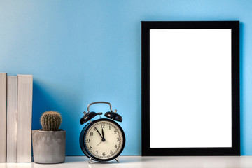 Black empty mockup frame on a blue background with a cactus, books and a black alarm clock