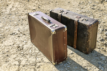 Two old suitcases on dry soil