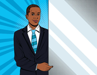Vector colorful pop art style illustration of a businessman holding a white banner. Handsome african american guy in suit showing to advertisement place