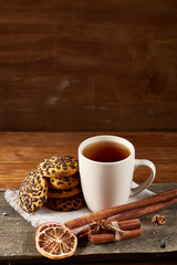 Cup of tea and chocolate chip cookies on white homespun napkin in country style, selective focus.