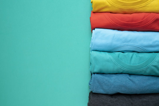close up of rolled colorful clothes on green background