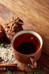 Christmas teatime with oatmeal, chocolate biscuits, and spices, on wooden background, close-up, selective focus.