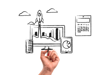 woman hand with pencil draws Rocket launch from PC monitor. PC monitor and tablet and smart phone width business chart on office desk. Concept of business start-up, boost or success