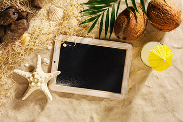 Summer vacation template background with empty blackboard on the sand. Top view with copy space.