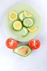 Sliced avocado and lemons on a green plate, avocado on white background, vegetarian food, useful natural food, tropical fruits for breakfast, copy space