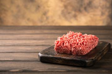Deurstickers Vlees Fresh raw beef minced meat on dark wooden board. Healthy food ingredients concept with copy space.