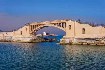 Bridge in the sea at Montazah park with calm sea and clear sky at sunrise time, Alexandria, Egypt