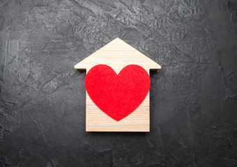 Red Heart inside a wooden house on a gray concrete background. The concept of a love nest, the search for new affordable housing for young couples and families. Favorite house, homesickness.