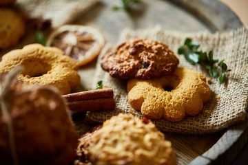 Conceptual composition with assortment of cookies and cinnamon on a wooden barrel, selective focus, close-up