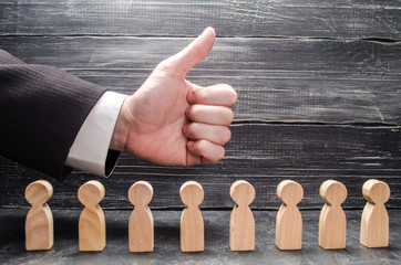 The businessman's hand shows a thumbs-up, above the figures of workers. The concept of approval of business ideas, congratulations on business success. Business development, promotion.