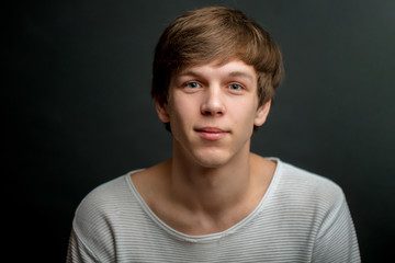 closeup portrait of handsome fair-haired guy with kind look isolated on the black background. kindness concept