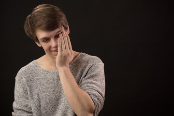 tired young man rubbing sleepy eyes isolated black background. copyspace