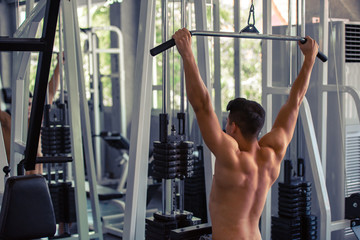 Portrait of young man using weight lifting equipment to build a massive chest and arm at indoor sport gym , bodybuilder concept.