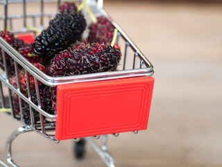 Close up group of mulberries in red shopping cart on wooden table. Mulberry this a fruit and can be eaten in have a red and purple color. Mulberry is delicious and sweet nature.