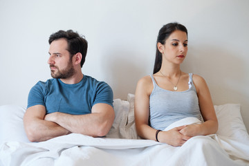 Angry girl and angry man in the morning lying in bed.Relationship difficulties