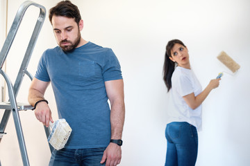 Tired man during home renovation arguing with girlfriend