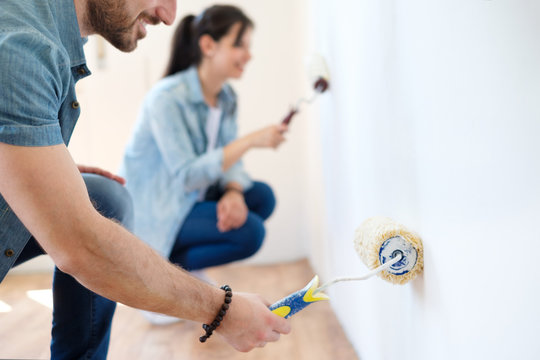 Portrait of smiling young couple painting interior wall of new apartment
