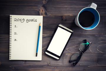 Notebook with 2019 goals massage with pencil, glasses, phone and cup of coffee on wood background.