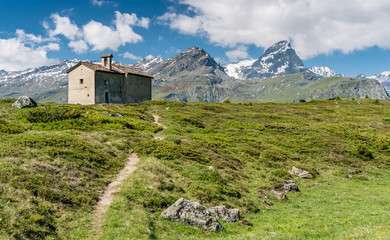 Wall Mural - mountain church in an idyllic mountain landscape in the summertime in the Alps with snow-capped peaks in the background