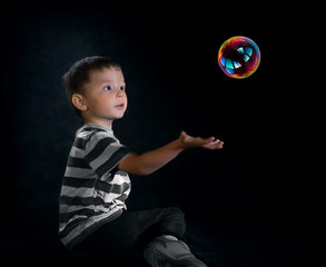 Young adorable 4 year old boy play with bubbles