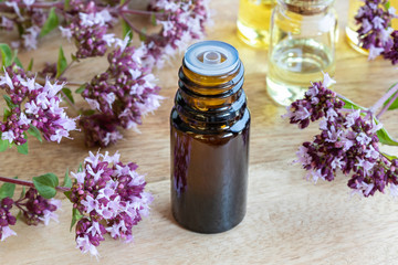 A bottle of oregano essential oil with blooming oregano twigs