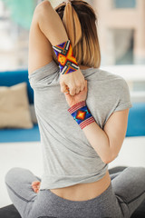 Close up of female hands with wristbands behind the back, woman practicing yoga, sitting in Cow Face exercise, Gomukasana pose, working out, wearing white sportswear, indoor, home interior background