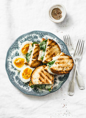 Healthy breakfast or snack - boiled farm eggs, spinach, grilled cheese sandwiches on light background, top view