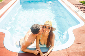 young beautiful couple in the pool at sunset