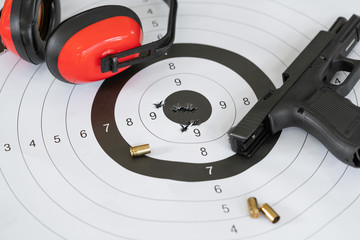 Close up shot of a shooting target and bullseye with bullet holes with automatic pistol gun and cartridge bullet.