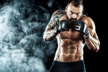 Sportsman boxer fighting on black background with smoke. Copy Space. Boxing sport concept.