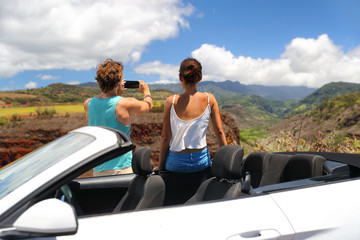 Wall Mural - Road trip car people taking phone pictures of nature landscape on summer travel vacation. Tourists couple taking photos on Hawaii Kauai island, with smartphone camera app.