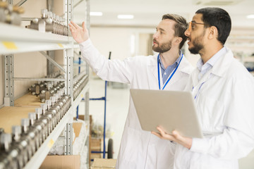 Two bearded technicians wearing lab coats standing at shelf of spacious manometer factory warehouse and taking inventory, one of them holding laptop in hands