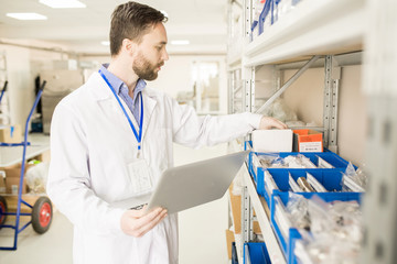 Concentrated bearded technician wearing lab coat checking existence of spare parts for  pressure sensors at spacious warehouse of modern factory and taking necessary notes on laptop.