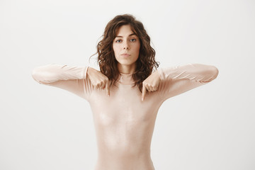 Studio shot of confident serious-looking female in beige outfit, pointing down, having no care what people think, standing self-assured over gray background as if naked, feeling ok show nipples