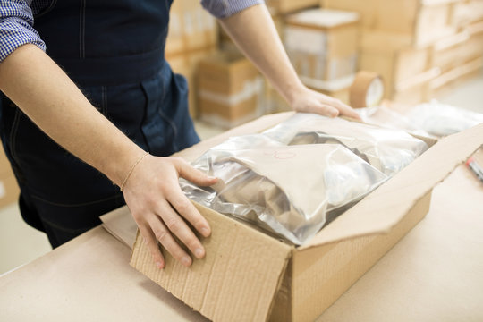 Close-up shot of male worker packing pressure sensors in cardboard box while working at warehouse of measuring equipment factory