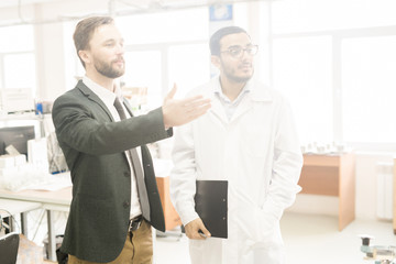 Bearded middle-aged businessman giving tour of production department of modern factory, young Arabian inspector wearing lab coat listening to him with interest