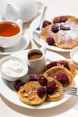 sweet corn pancakes with berries for breakfast, vertical top view