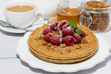 traditional thin pancakes with fresh raspberries for breakfast on wooden table, closeup