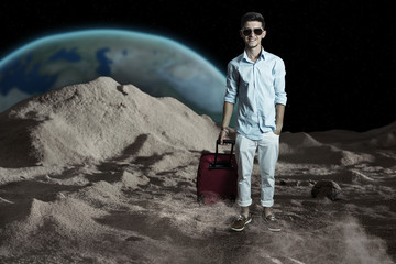smiling tourist with baggage walking on the moon in front earth